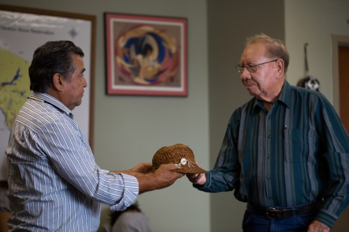 """Lummi Elder Sit-ki-kadem (Doug James) gifts a traditional red cedar hat to Leo O'Conner, Elder and Tribal Treasurer from the Ihanktonwan Oyate (Yankton Sioux). O'Conner was the last person born in the Ihanktonwan village of White Swan that was flooded in 1952 by an Army Corp of Engineers hydroelectric dam project that took place without consent from the Ihanktonwan People. The tribe lost almost 3,000 acres of their homelands when the Fort Randall dam closed. """"On this journey over here I knew this hat was going to be given away, but I didn't know where, and I didn't know who,"""" Sit-ki-kadem said. The cedar hat was woven by Tsilixw (Bill James), the Hereditary Chief of the Lummi People, and passed on to Sit-ki-kadem years ago."""