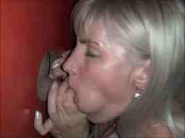 Blonde MILF wife gives a sloppy blowjob at the porn booth glory hole