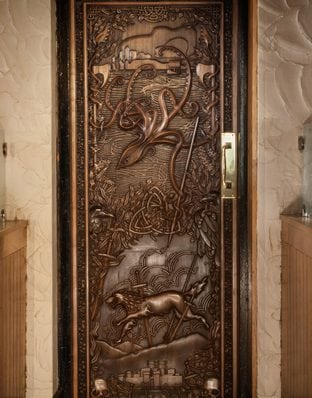 Game of Thrones Door at Percy French's in Newcastle. Depicting a ship leaving from Greyjoy's Iron Islands with a direwolf below the shipl.