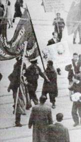 Η άγνωστη φωτογραφία (όχι του Ντμίτρι Κέσελ) από τα Δεκεμβριανά, 03/12/1944, Πλατεία Συντάγματος. Ο Μίκης Θεοδωράκης με μια ματωμένη σημαία, που, όπως έχει πει σε συνεντεύξεις του, τη βρήκε και την βούτηξε στο αίμα των νεκρών στο έδαφος.