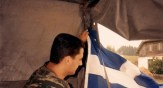 Βοσνία, 1995. Διακρίνεται ένας Ελληνας εθελοντής της ΕΕΦ, ο Κωνσταντίνος Καλτσούνης (βαμμένος χρυσαβγίτης που λέγεται ότι αυτοκτόνησε τέλη Μαρτίου 2016 λόγω οικονομικών προβλημάτων) με ελληνική σημαία σε αντίσκηνο.