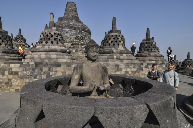 Tourists inspect a Buddha statue at Borobudur Temple in Magelang, Central Java, Indonesia, Aug. 12, 2019.