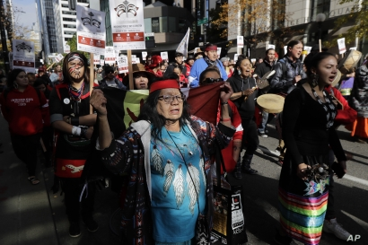 People taking part in a rally to mark Indigenous Peoples' Day in downtown Seattle sing as they march toward Seattle City Hall,…