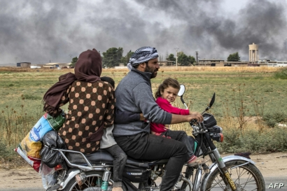 Members of a Syrian family use a motorcycle to flee the countryside of the northeastern Syrian town of Ras al-Ain on the…