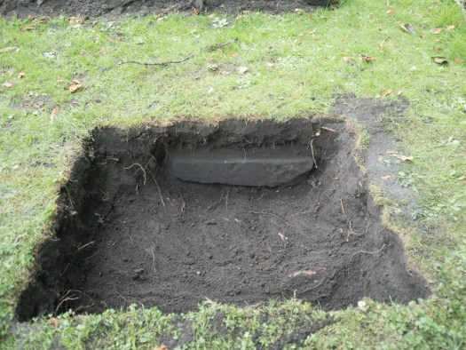Right in the side of the test pit another gravestone revealed