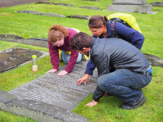 The 2019 volunteer supervisors, Jo, Cass and Rob (left to right) examine a headstone with inlaid lettering.