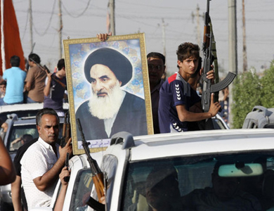 Volunteers, who have joined the Iraqi Army to fight against predominantly Sunni militants, carry weapons and a portrait of Grand Ayatollah Ali al-Sistani during a parade in Sadr city