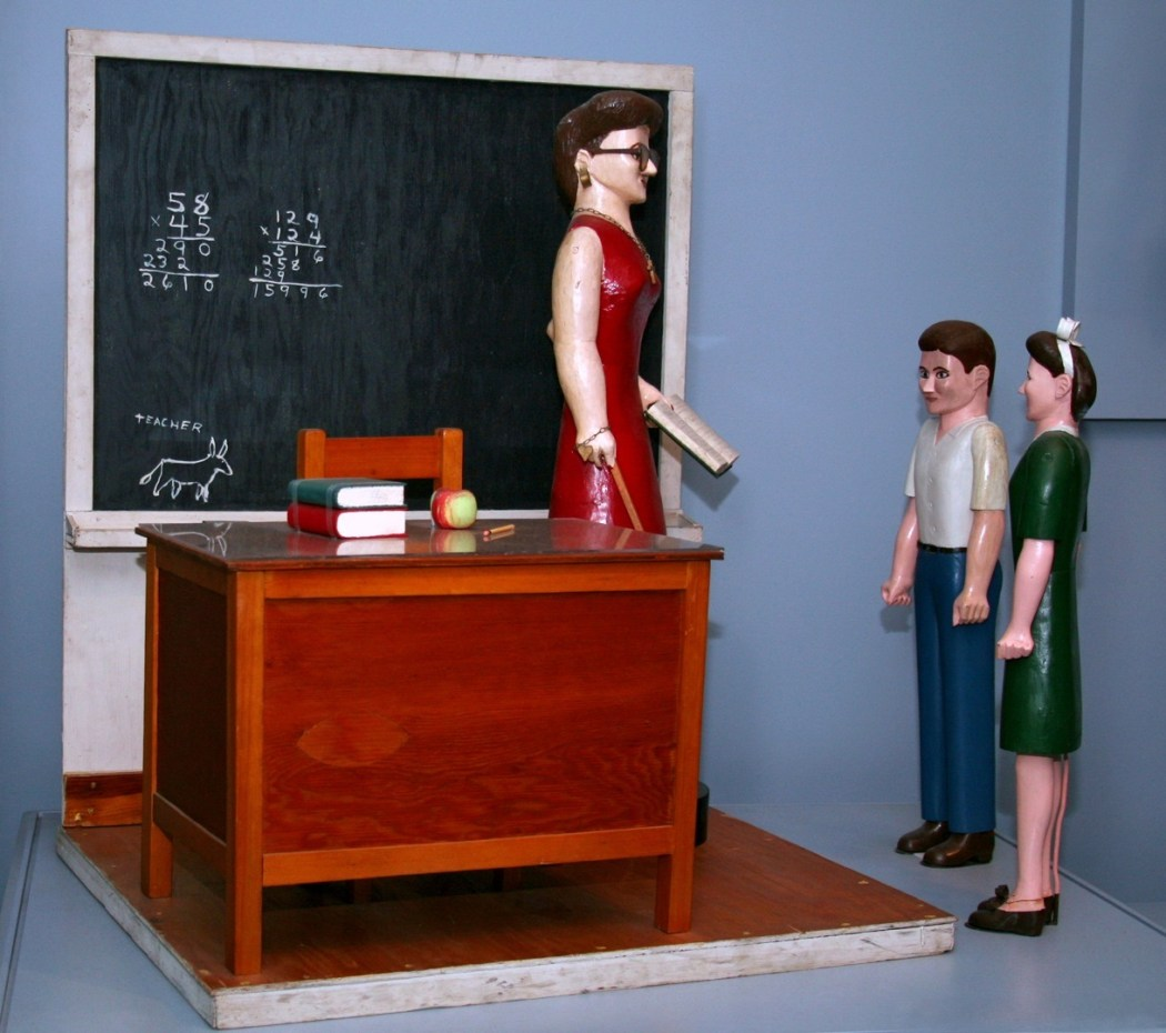 Photograph of three figurines in a classroom