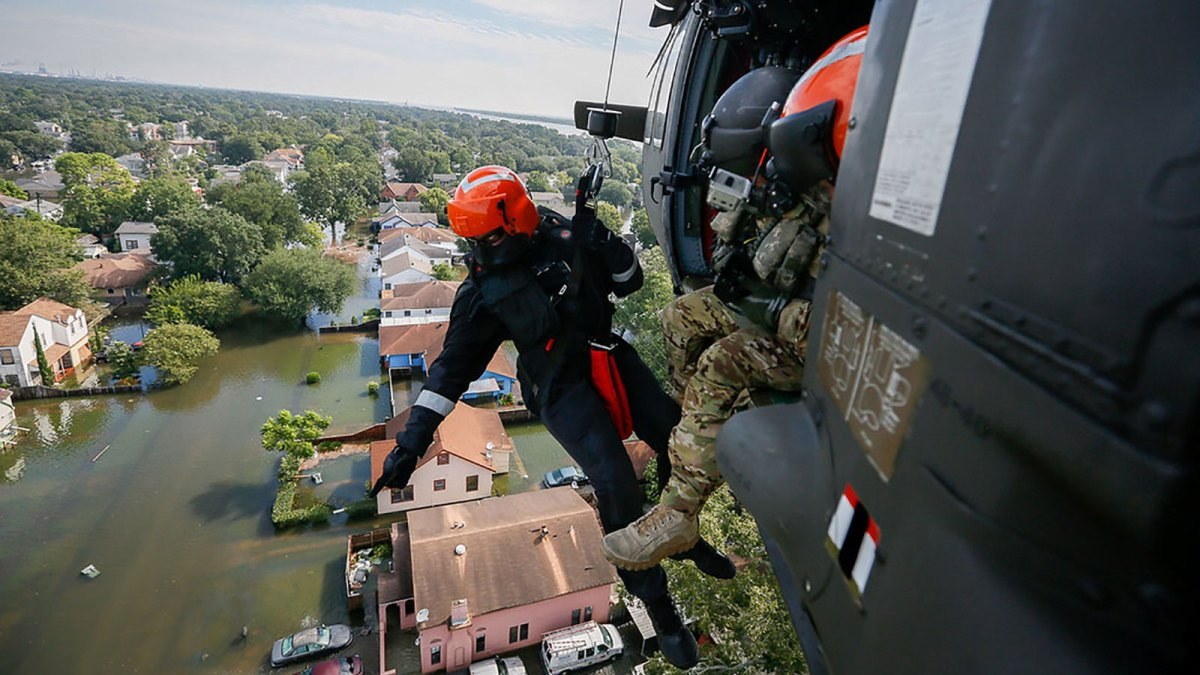 National guard members look over flooding from a helicopter.