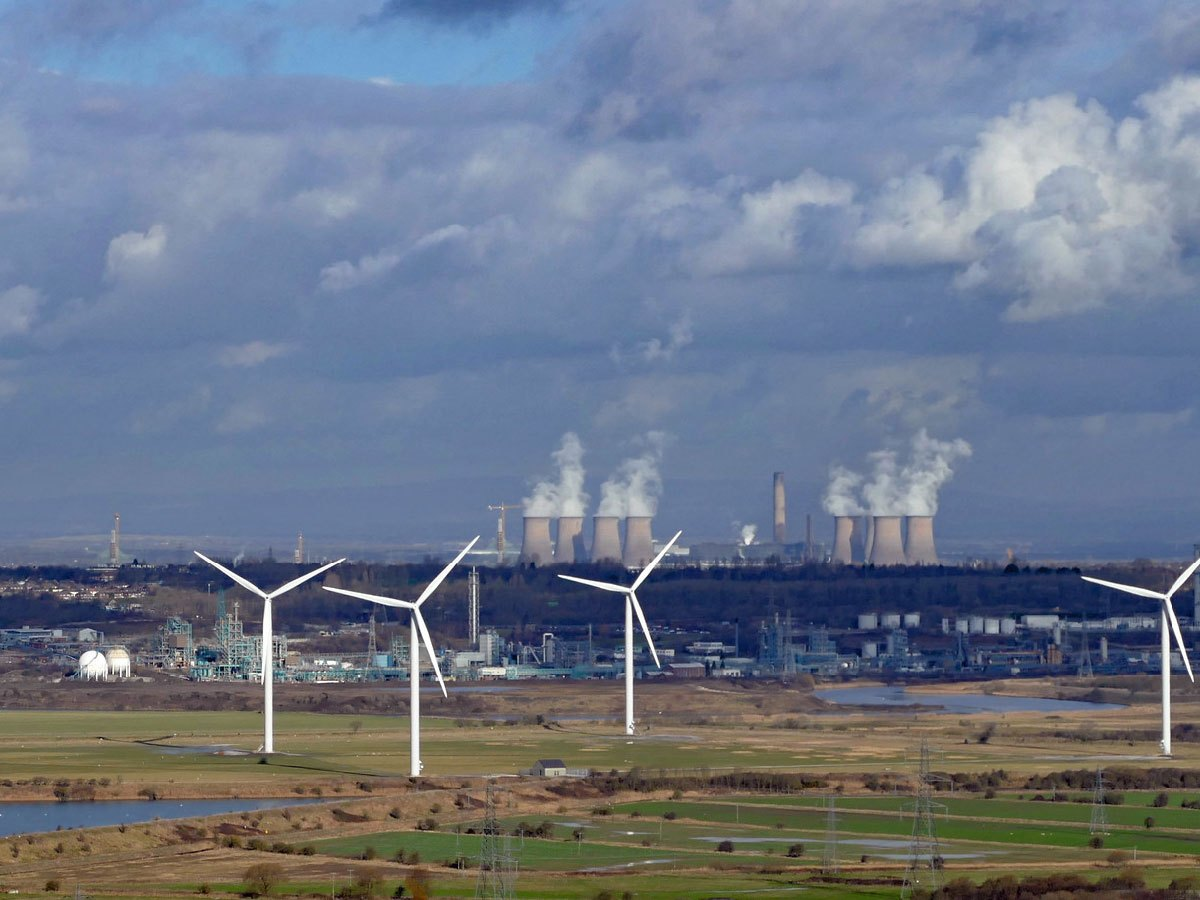 Wind farm with coal plant in the background.