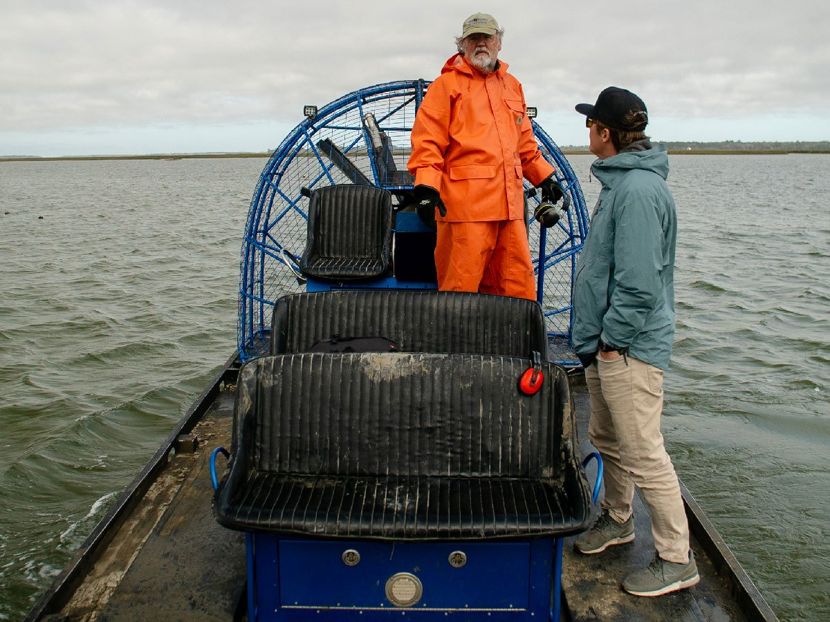 A clam farmer steers a boat.