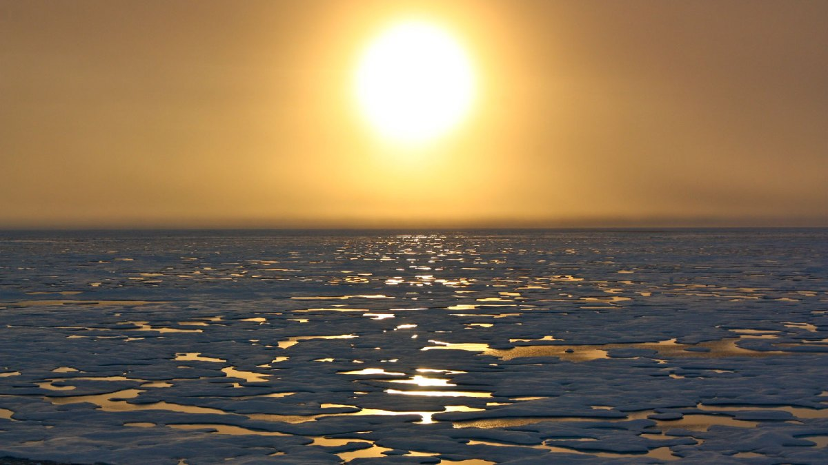 The sun sets over melting Arctic ice