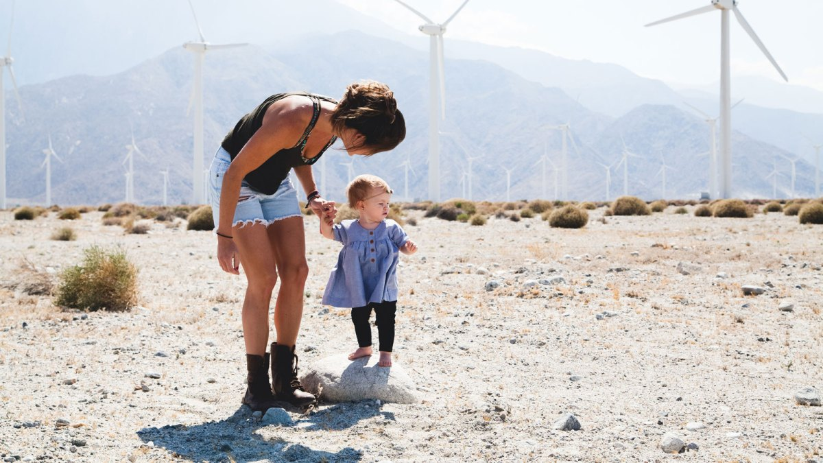 Mother, child, and wind turbines in background