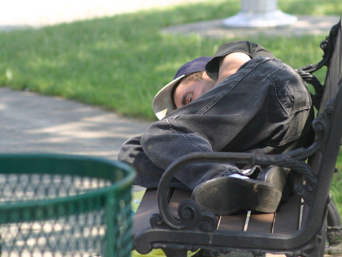 A man sleeps on a bench in a park
