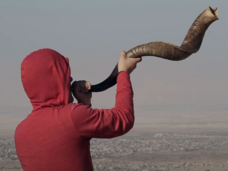 Man playing ram's horn trumpet