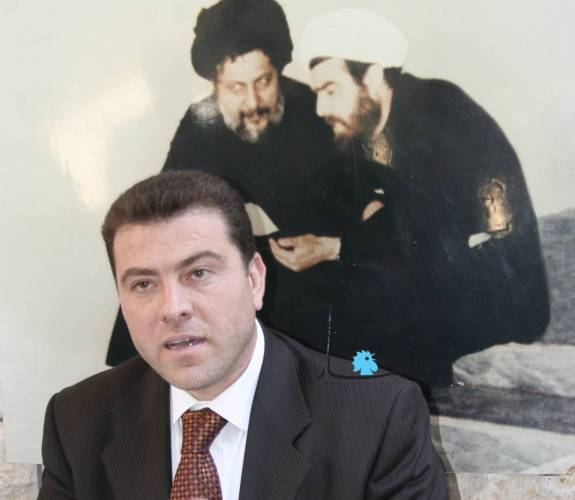 Forer  Hezbollah MP Hassan Yacoub. The background  shows a portrait of his father Sheikh Mohammed Yacoub (R)  –  with AMAL Movement founder Imam Moussa al-Sadr