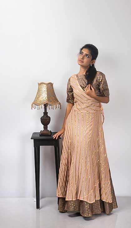 Brown Zari weaved Gown is paired with a Peach Half Angrakha patterned Jacket. The Jacket is embroidered with thread and sequins work.