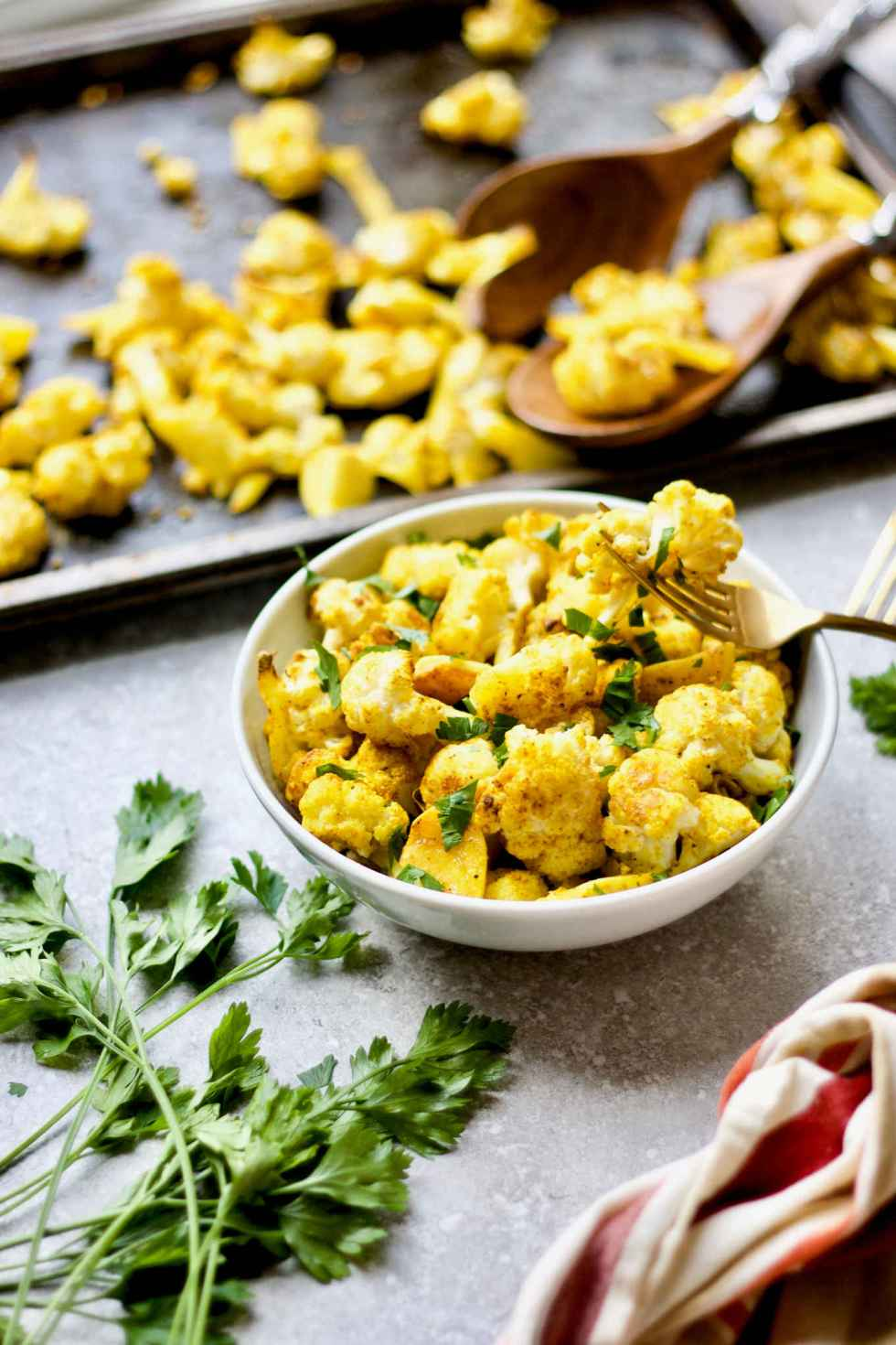 Garlic turmeric roasted cauliflower served in a bowl. The turmeric and garlic gives the roasted cauliflower an anti-inflammatory and immune boost.