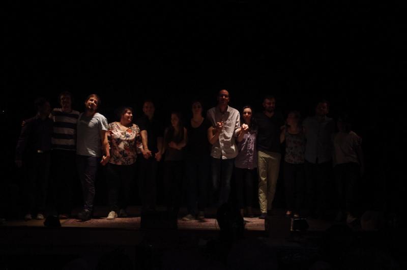 13 personnes saluent sur une scène de théâtre