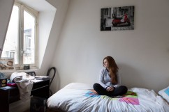 """15 février 2016, Paris, France. Philippine a 20 ans. Elle vit dans une chambre de bonne dans le 16 ème arrondissement de Paris. Elle est membre de l'Action Française, un groupe royaliste et nationaliste. Son militantisme a démarré à l'âge de 17 ans, lors du camp d'été Maxime Real Del Sarte auquel son père lui a proposé de participer. Ses études d'histoire-géographie devrait lui permettre de travailler un temps, """"jusqu'au moment où [elle] aura des enfants."""" Elle n'a pas d'inquiétude pour son avenir professionnel, mais se demande si elle élèvera correctement ses enfants et si elle sera sainte jusqu'au bout."""