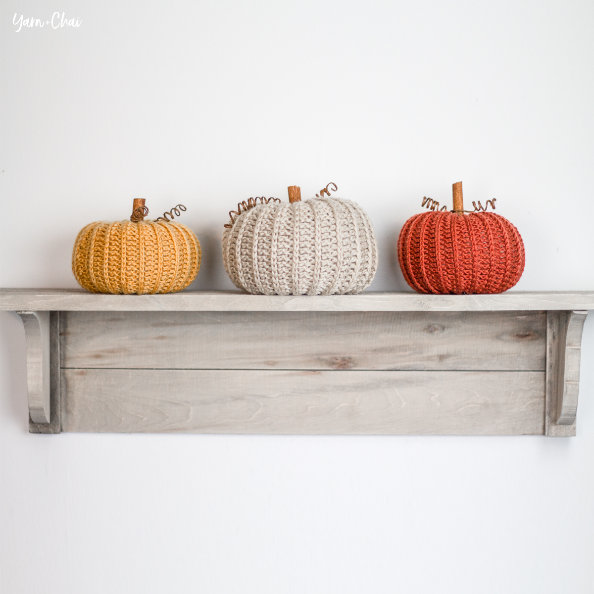 three autumn colored knitted pumpkins on a shelf