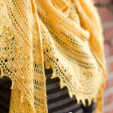 a yellow lace shawl worn over a woman's grey striped coat