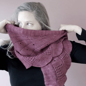 Pink shawl covers a white model's face.