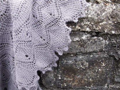 a violet tunisian crochet shawl laying on top of a granite stone. The shawl is made up of lots of fans interspersed with short rows for texture and shaping