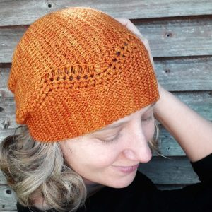 a white woman wears a warm yellow hat with a knit garter stitch band and a Tunisian crochet crown. The border between the two crafts is a zig zag that makes the hat look a little like a crown.