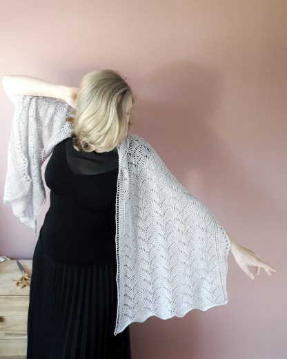 a white woman wears a grey lace shawl across her shoulders with one arm outstretched. Her face is obscured by her blonde hair. She is dressed in black and stands in front of a light pink wall