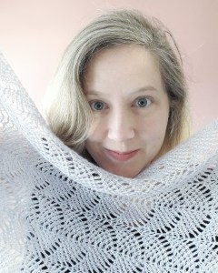 close up of a white woman's face smiling over a grey lace shawl