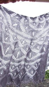 close up of sun shining through a violet tunisian crochet shawl