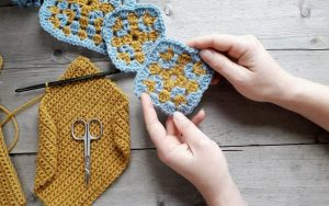 close up of a pair of hands holding a two colour granny square close to a selectionof similar squares. Also on the table is a sheet of yellow crochet fabric and a small scissors