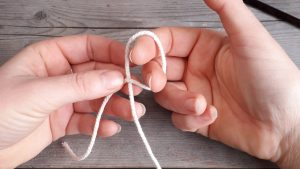 the index finger and middle finger of the right hand have been poked upward through a loop made by the crossed strands of yarn