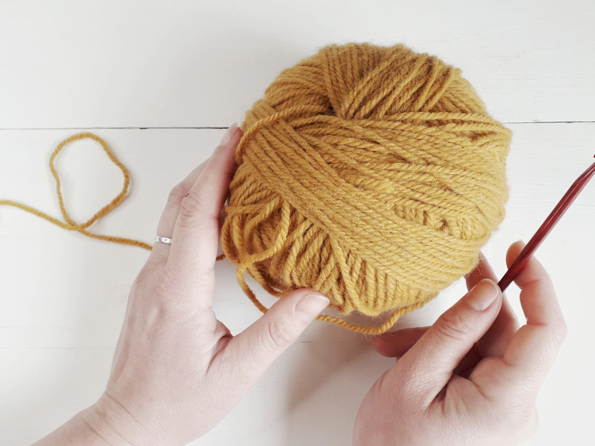 two hamds hold a large ball of warm yellow yarn on top of a painted white wooden surface. In the right hand is a crochet hook