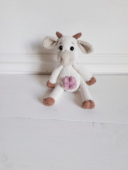 a white, crochet cow toy, sits against a white wall