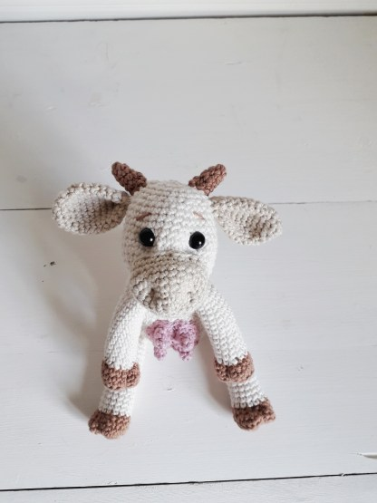 an midshot of a white, crochet cow toy, looking into the camera while sitting on a white table top