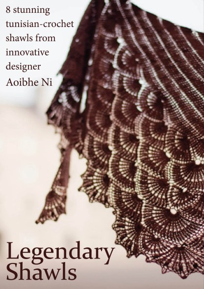 Brown shawl held up over a light background. The shawl is made up of interlocking shells