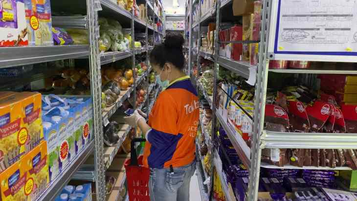 Inside a talabat Mart dark store showing a staff scanning an item as part of an existing order