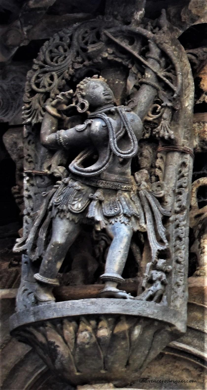 Madanike hunting a bird - A bracket figure mounterd on the exterior wall of the Belur Chennakeshava Temple in Karnataka, India