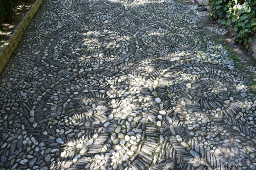 Mosaic on the walkway paved with black and white pebbles in Generalife, Granada, Spain