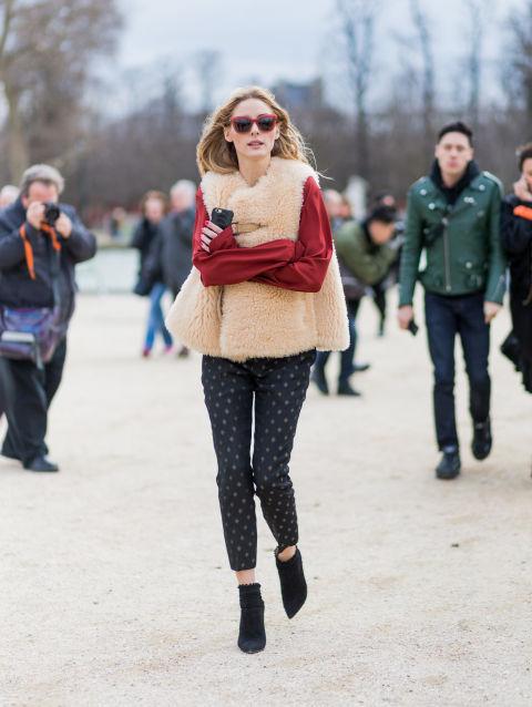Объёмный жилет из меха бежево-розового оттенка, который контрастирует с шёлковой бордовой блузой и обтягивающими брюками от Оливии Палермо
