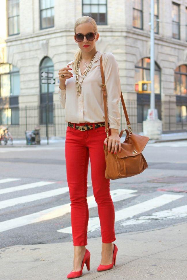 Красные брюки с бежевой блузой и светло коричневой сумкой.