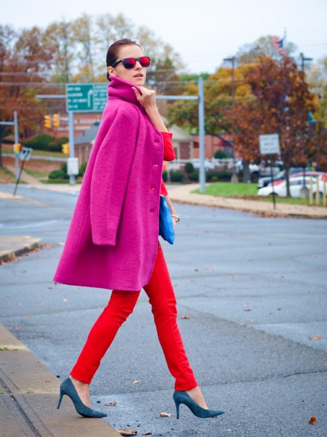 Красные брюки с драповым пальто цвета фуксии.