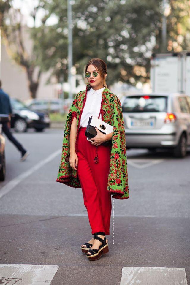 Красные брюки с пончо ярко зеленого цвета с ярким цветочным принтом.