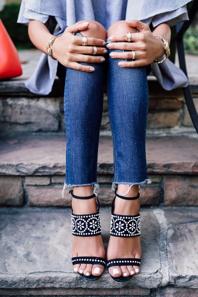 Топ с открытыми плечами нейтрального серого цвета, джинсы с разрезами на коленях и босоножками на массивном каблуке.