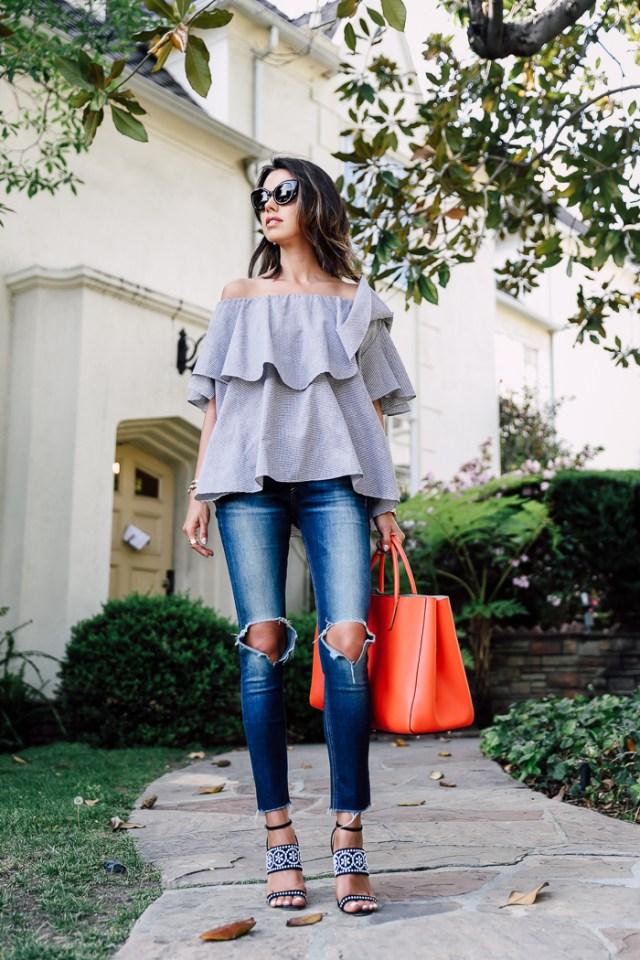 Топ с открытыми плечами нейтрального серого цвета, джинсы с разрезами на коленях, босоножками на массивном каблуке и яркая красная большая сумка.