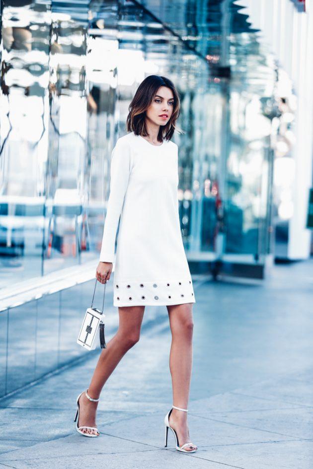 На фото: белое платье прямого покроя, длиной выше колена с длинным рукавом.