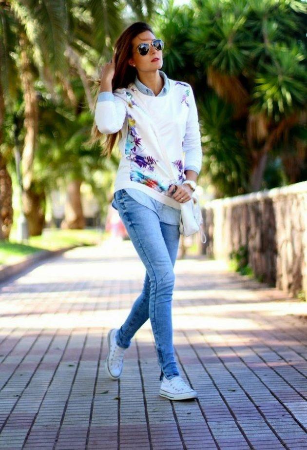 На фото: белые кеды Converse в сочетании с джинсами и блузой.