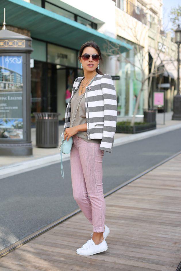 На фото: белые кеды Converse в сочетании с розовыми джинсами и пиджаком с принтом в полоску.